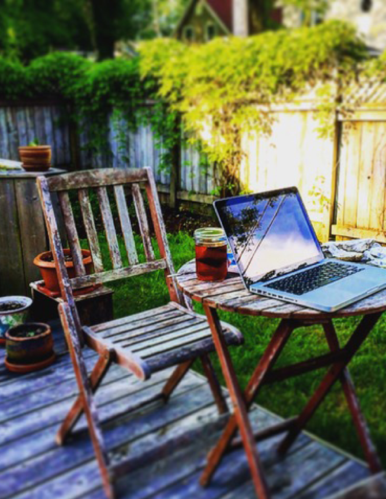 Laptop computer on an outdoor table, set up for writing
