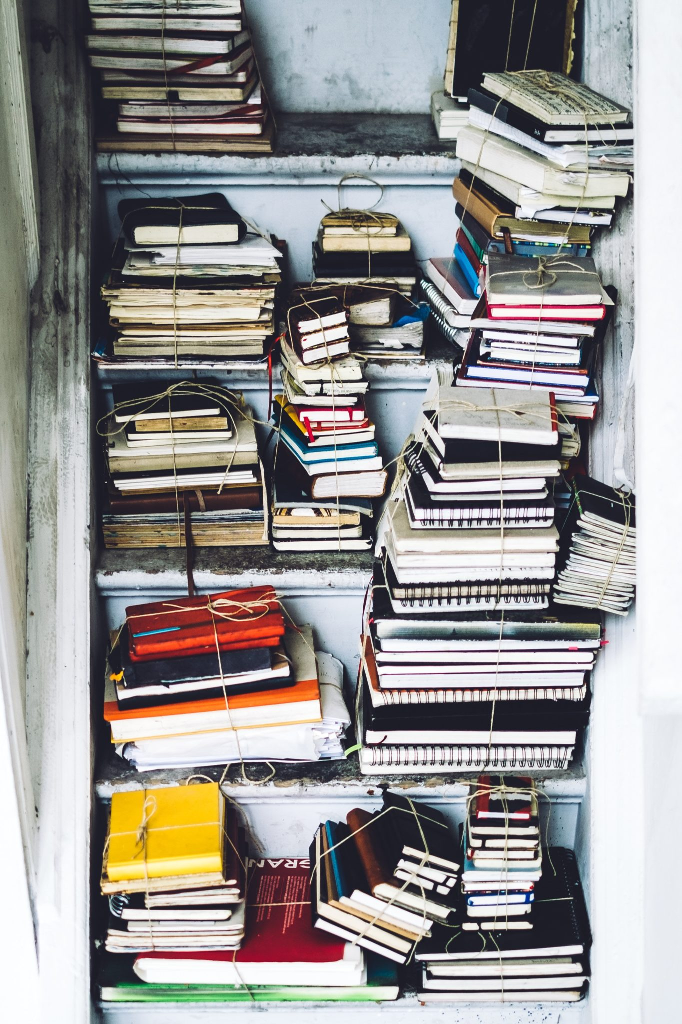 Stacks of writing journals, bound with string, on wooden bookshelf